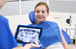dentist holding x-ray on tablet