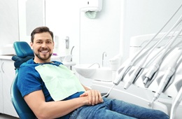 Man in blue shirt in dental chair looking at camera