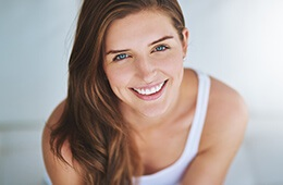 woman in white tank top smiling