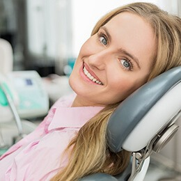 woman in pink laying in dental chair