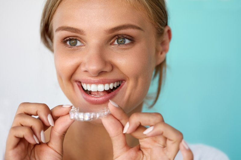 A woman holding a clear aligner.