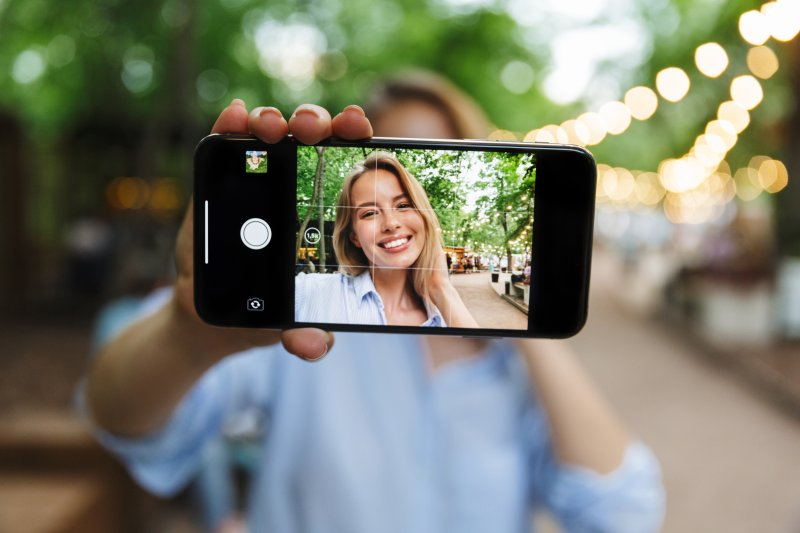 Woman using her phone to take a video of herself