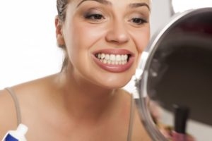 woman looking in the mirror for signs of teeth shifting